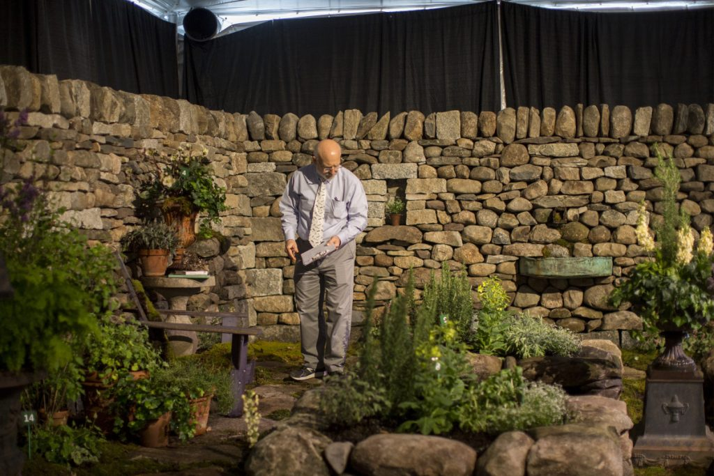 Gary Fish, state horticulturist, judges the Maine Stonework garden display at the 2018 Maine Flower Show.