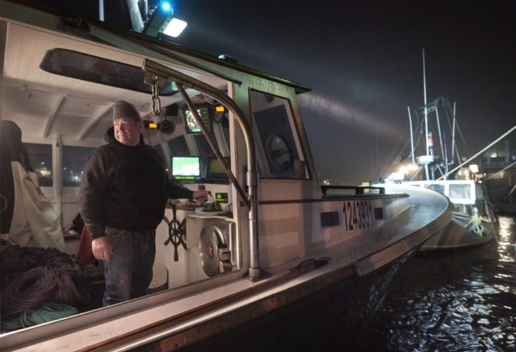 Lobsterman John Williams, 63, of Stonington steers his boat away from the dock early Friday. Four years ago, Williams and his wife had a $750 health insurance deductible; today it's $5,400. The couple look forward to turning 65, when they'll be Medicare-eligible.