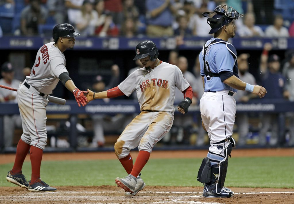 Boston's Mookie Betts, center, slaps hands with on-deck batter Xander Bogaerts, left, after scoring past Tampa Bay Rays catcher Wilson Ramos on an RBI single by J.D. Martinez in the fifth inning of a the Red Sox' 2-1 win Sunday in St. Petersburg, Florida.