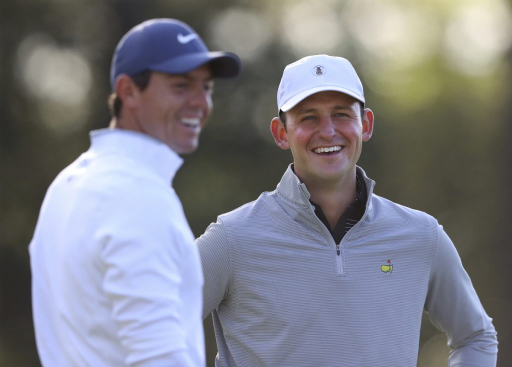 Matt Parziale, right, the U.S. Mid-Amateur champion who works as a firefighter in Brockton, Massachusetts, shares a laugh with Rory McIlroy during a practice round for the Masters golf tournament Monday in Augusta, Georgia. (Curtis Compton/Atlanta Journal-Constitution via AP)