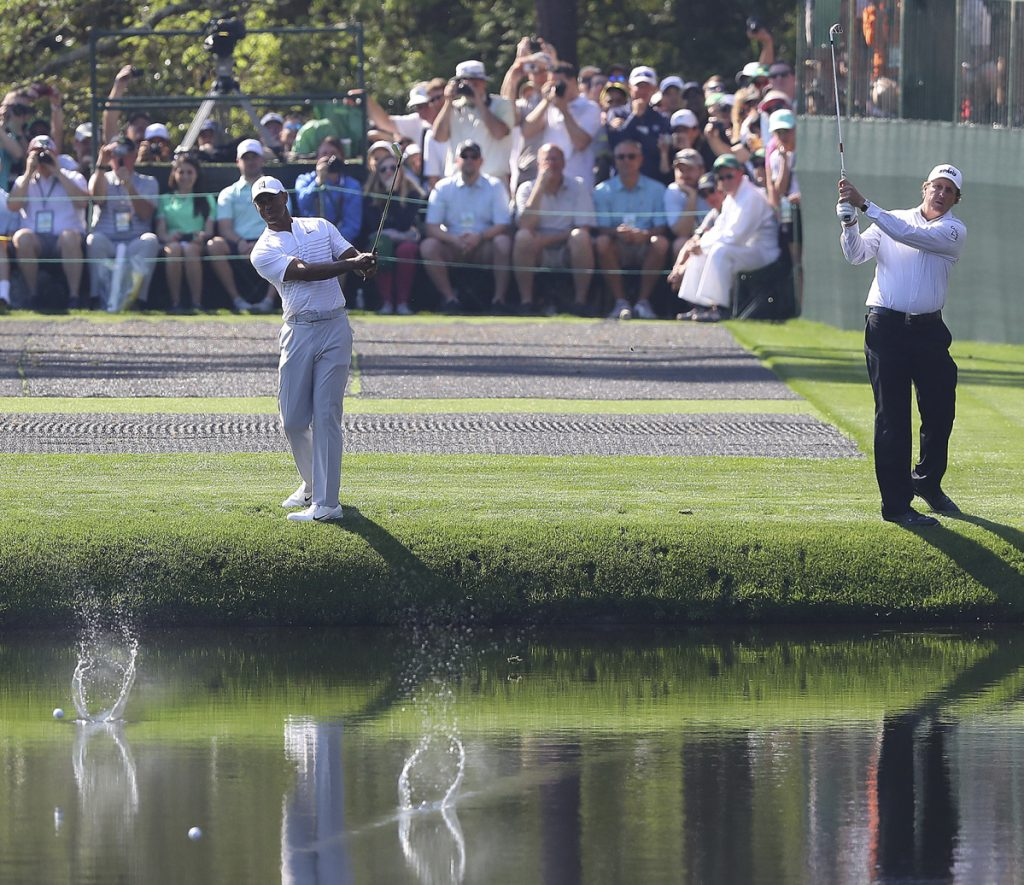 Tiger Woods, left, and Phil Mickelson skip their shots across the pond to the 16th green while clowning around for the crowd during a practice round at Augusta National Golf Club on Tuesday.