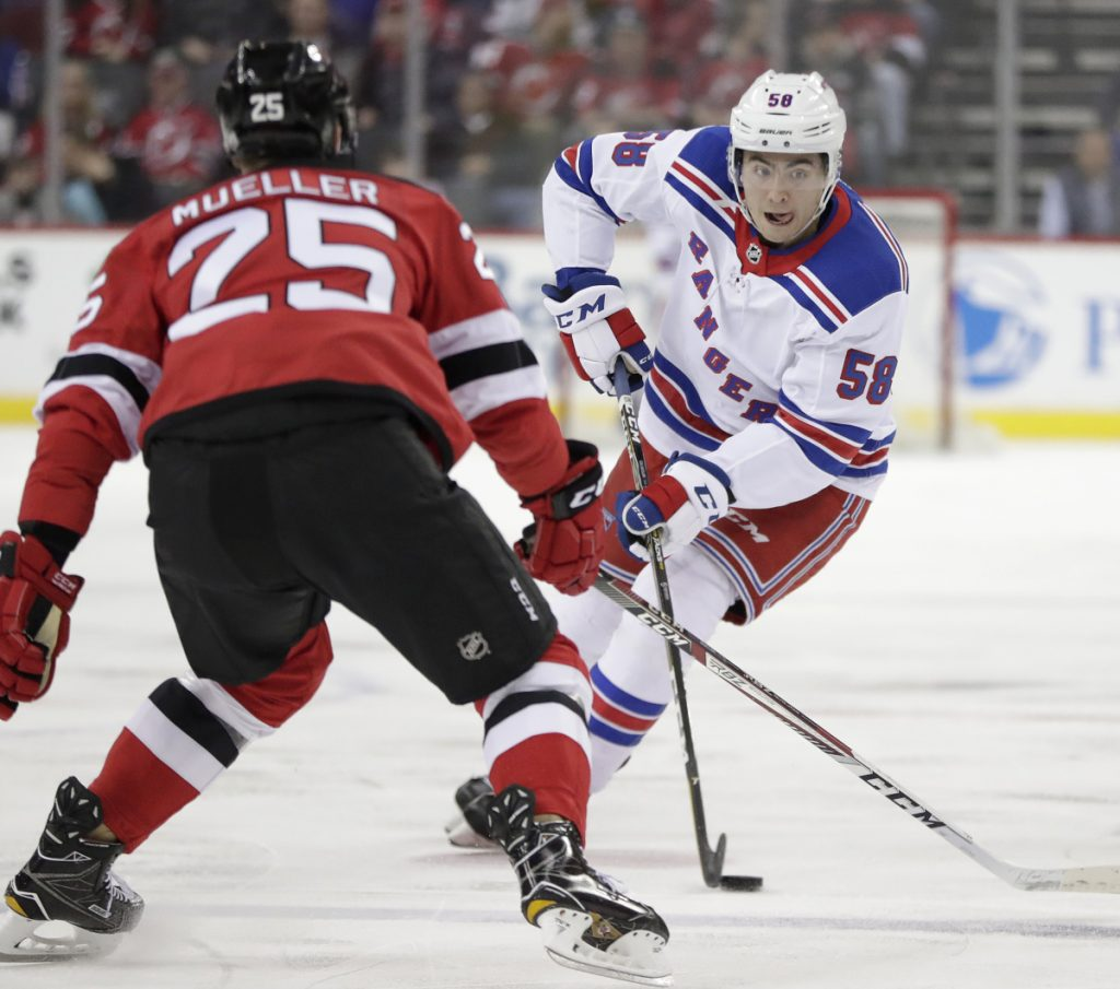 Rangers defenseman John Gilmour tries to skate into the zone against New Jersey defenseman Mirco Mueller Tuesday.