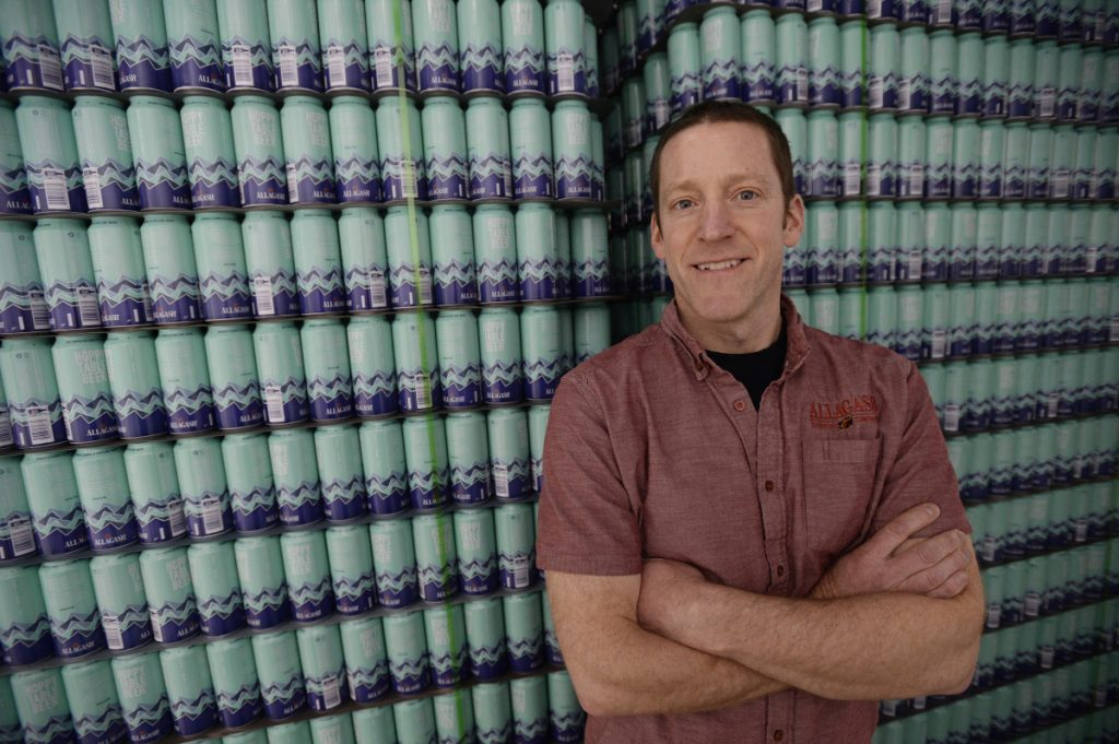 Allagash brewmaster Jason Perkins stands near a stack of 16-ounce cans that will soon be filled with Hoppy Table Beer as the Portland company – and Maine's largest brewery – tests out a container other than bottles. Canning is