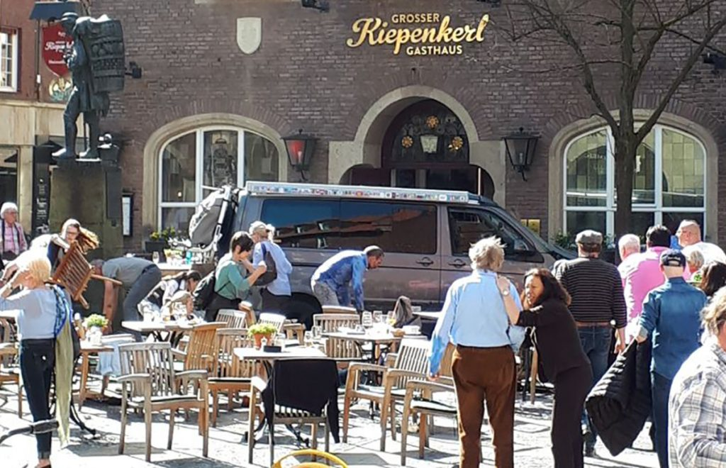 People react in front of a popular bar Saturday in Muenster, Germany, where a van crashed into a group of people, killing two and injuring 20. The driver shot himself to death inside the van.