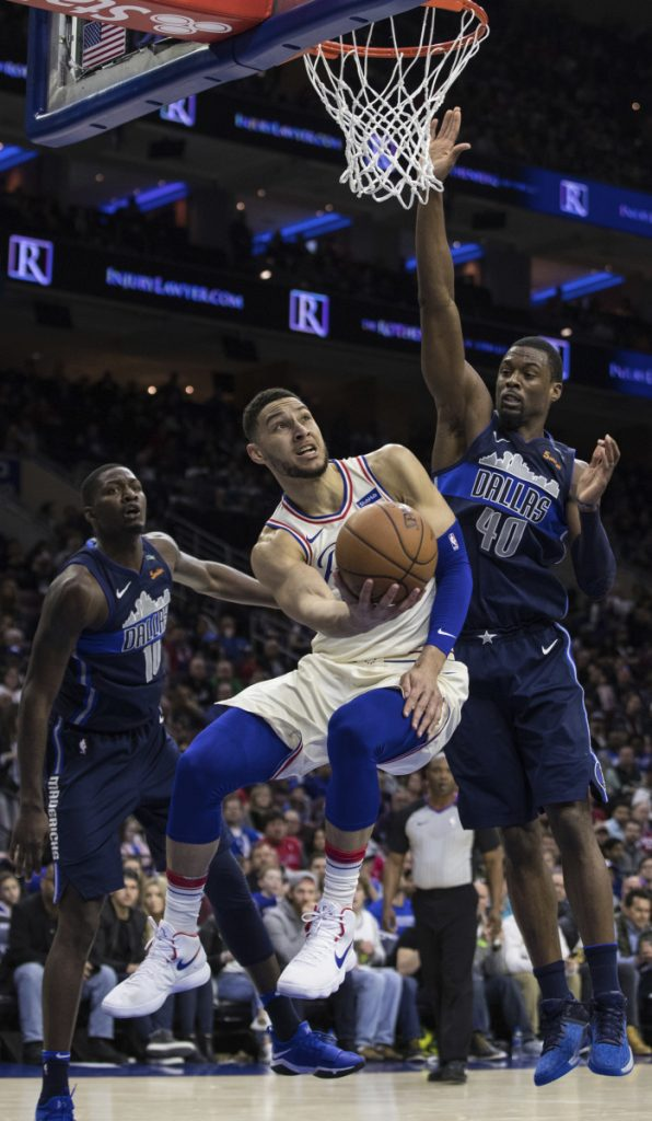 Ben Simmons of the Philadelphia 76ers finds room Sunday between Dorian Finney-Smith, left, and Harrison Barnes of the Dallas Mavericks.