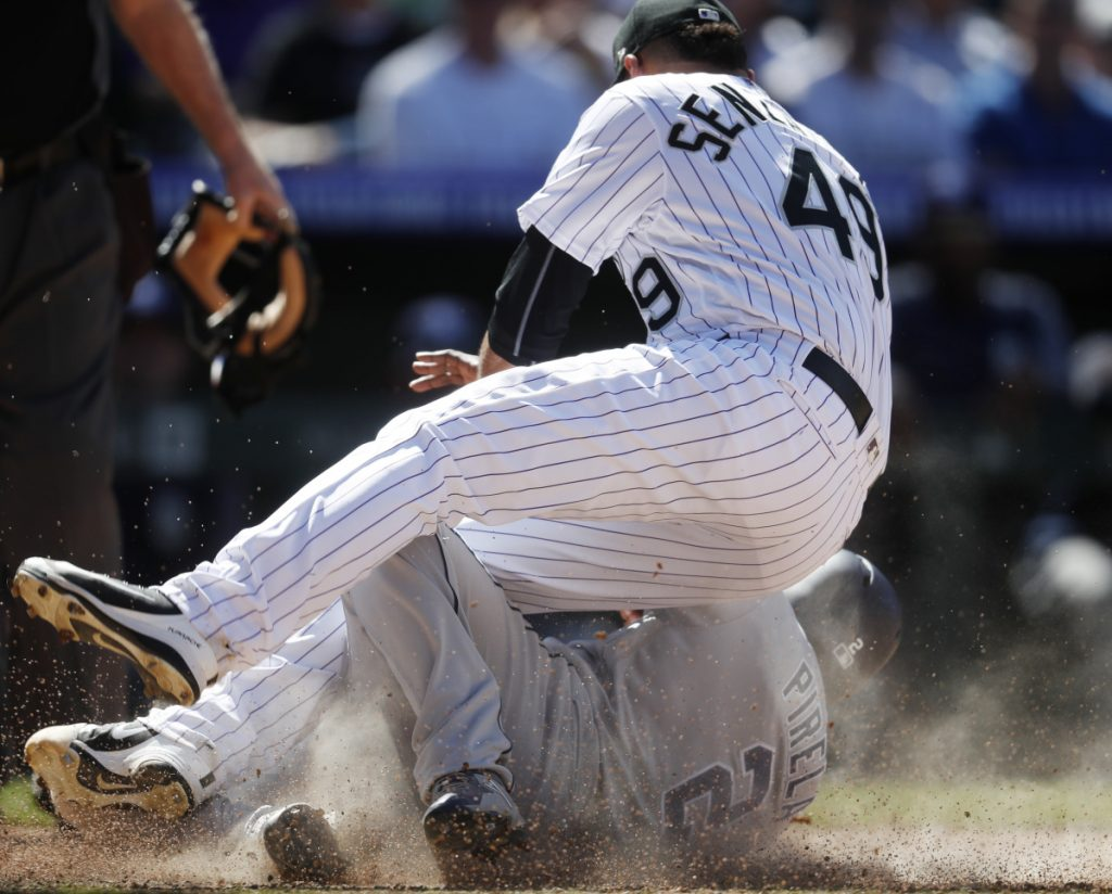 Rockies relief pitcher Antonio Senzatela lands on the Padres' Jose Pirela, who scored on a passed ball in the sixth Wednesday in Denver. The Rockies won the brawl-marred game 6-4.