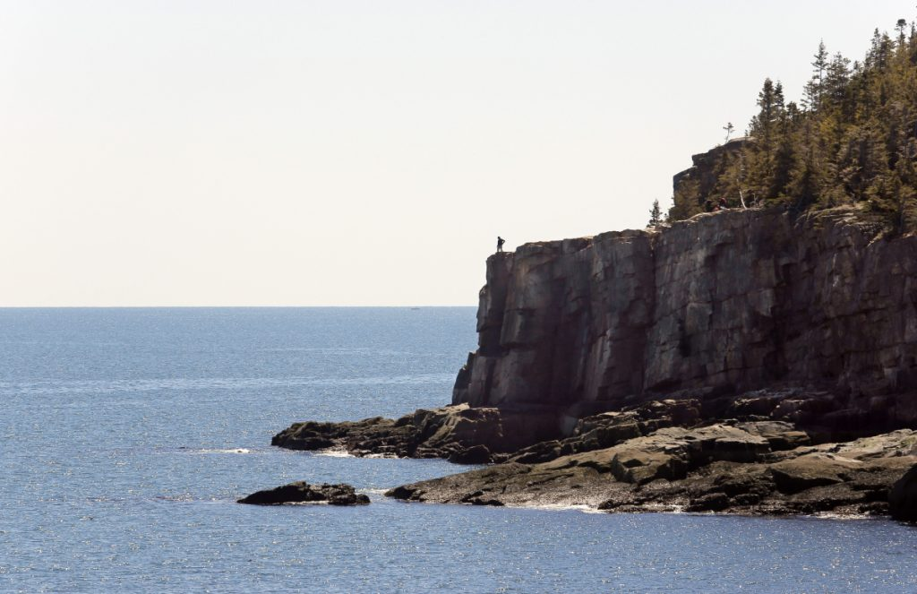 MOUNT DESERT ISLAND, ME - APRIL 30: A lone visitor looks out over the ocean from Otter Cliffs in Acadia National Park on Saturday, April 30, 2016. Many locals take advantage of the quiet shoulder seasons in spring and fall, when the crowds are absent from the park. (Photo by Gregory Rec/Staff Photographer)
