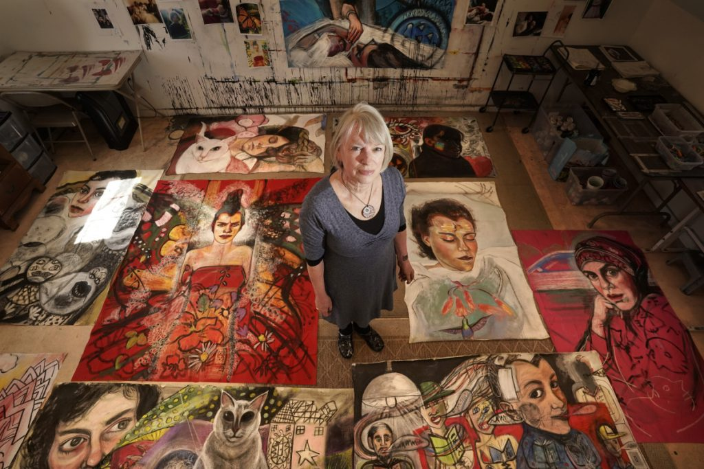 "Martha Miller poses for a photo with paintings from her current project, the ""Lisbeth Series,"" in her studio in Woolwich. Over the past several weeks, Miller has been creating highly graphic, sometimes disturbing and sometimes beautiful images of her daughter, who is disabled."