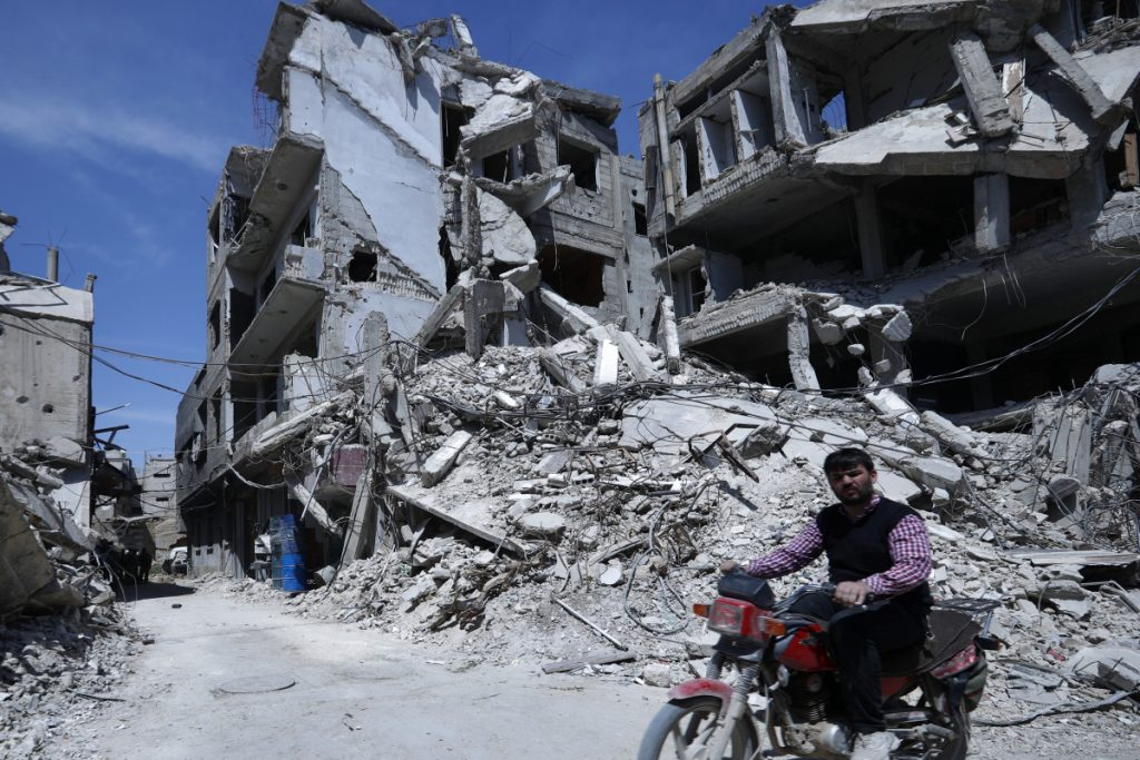 "A man rides past destruction in the town of Douma, the site of a suspected chemical weapons attack, near Damascus, Syria, Monday, April 16, 2018. Faisal Mekdad, Syria's deputy foreign minister, said on Monday that his country is ""fully ready"" to cooperate with the fact-finding mission from the Organization for the Prohibition of Chemical Weapons that's in Syria to investigate the alleged chemical attack that triggered U.S.-led airstrikes. (AP Photo/Hassan Ammar)"