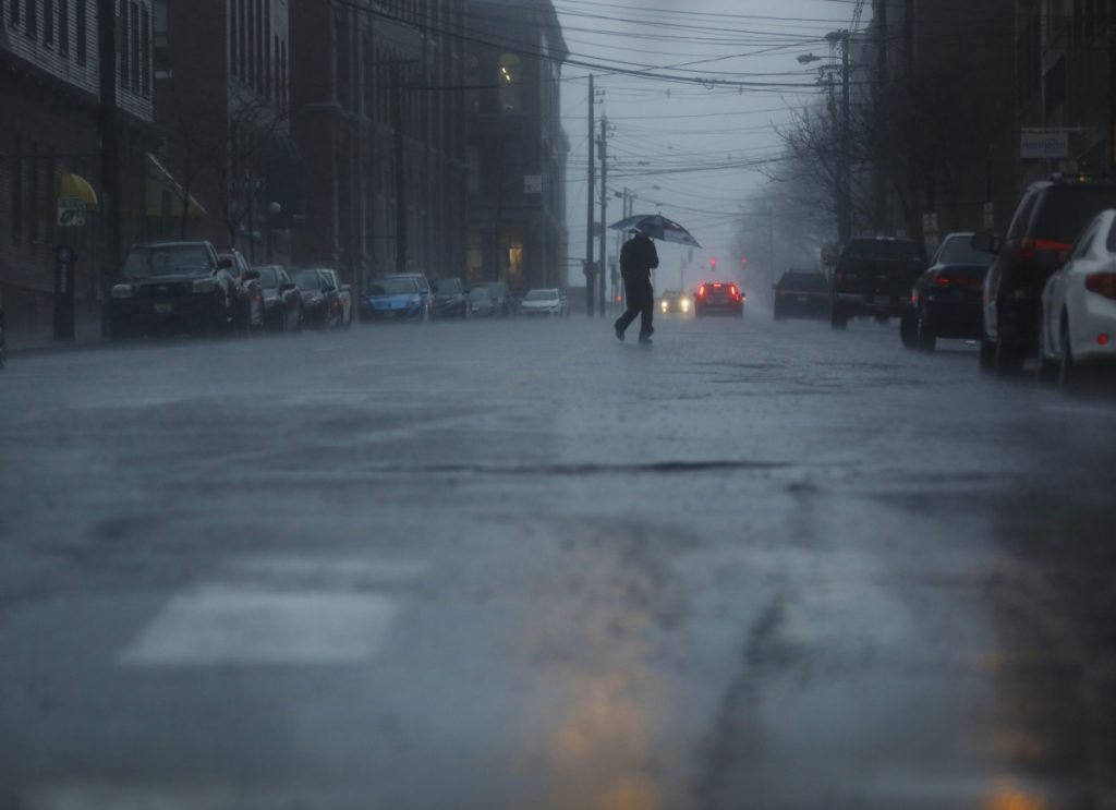 A man crosses Pearl Street in the rain on Monday. There were widespread power outages and flooded roads from the storm.