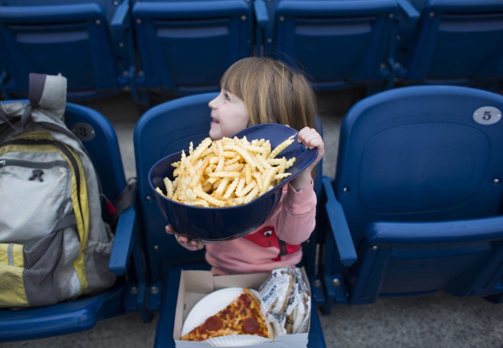 Portland restaurateurs Andrew and Briana Volk's daughter, Oona, holds a helmet full of fries at the Sea Dogs' home opener Friday.