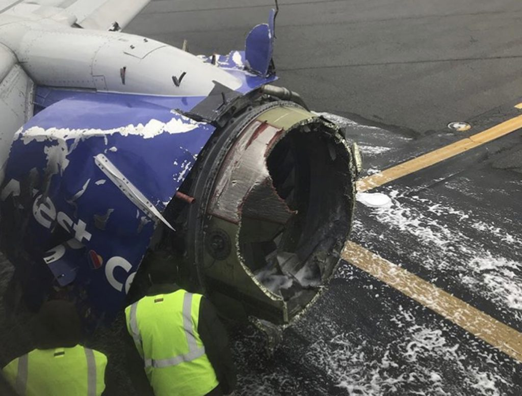 The engine on a Southwest Airlines plane is inspected as it sits on the runway at the Philadelphia International Airport after it made an emergency landing in Philadelphia, on Tuesday.