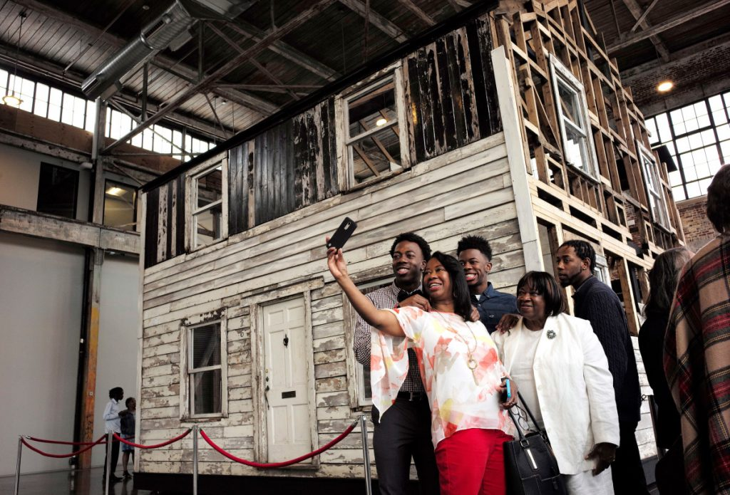 Cheryl Galloway of Providence, R.I., front, uses a mobile phone to take a photo with family members in front of the rebuilt house of Rosa Parks in Providence earlier this month.