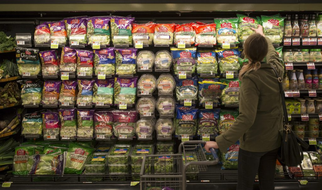 Sarah Moak grabs a bag of pre-packaged romaine lettuce hearts from a shelf in the South Portland Hannaford off of Cottage Road. Moak said that she trusts Hannaford to make sure their romaine is safe.
