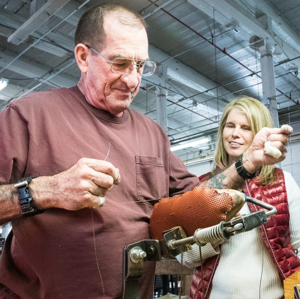 Mary Mayhew, right, watches Quoddy hand sewer Paul Leathers make a pair of boat shoes at the Lewiston shoe shop Friday morning. Leathers has been sewing for a number of companies since 1963.