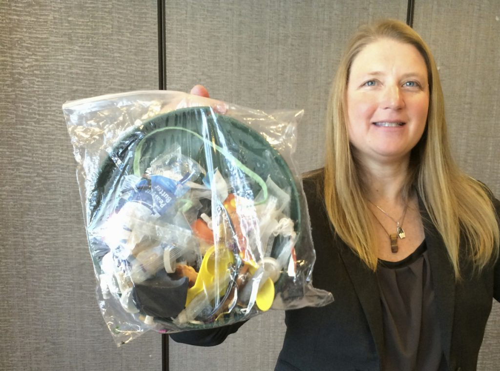 Jenna Jambeck, an environment engineering professor at the University of Georgia, holds a bag of trash collected last fall from a cleanup at Panama Beach, Fla.