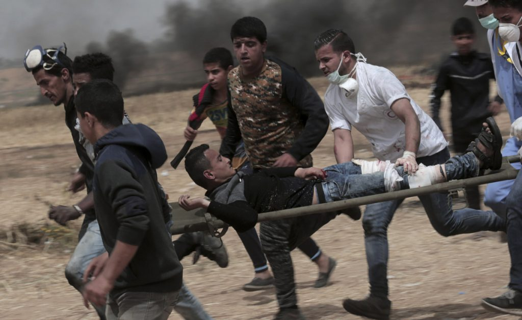 Palestinian protesters evacuate a wounded youth during clashes with Israeli troops along Gaza's border with Israel, east of Khan Younis in the Gaza Strip on Friday.
