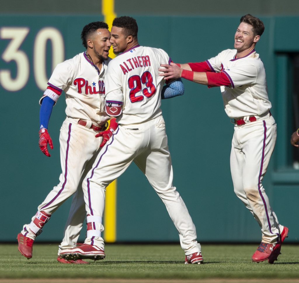 Aaron Altherr celebrates with Phillies teammates J.P. Crawford, left, and Andrew Knapp after his 11th-inning single Sunday beat Pittsburgh, 3-2.