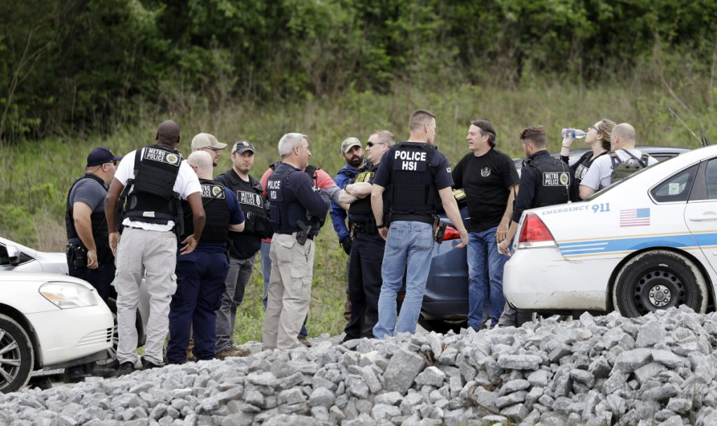 Police gather on a road along a wooded area where Waffle House shooting suspect Travis Reinking was captured Monday in Nashville, Tenn. His father, who returned his son's guns to him after they were seized by law enforcement, could face charges.
