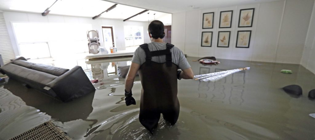 Gaston Kirby walks through floodwater inside his home last September in the aftermath of Hurricane Harvey, which sent the Addicks and Barker reservoirs over their banks in Houston.