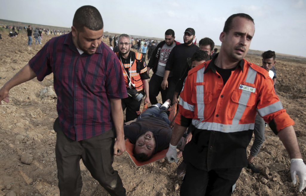 Palestinian medics carry a wounded man during a protest at the Gaza Strip's border with Israel on Friday.