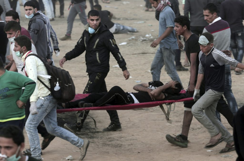 Palestinian protesters evacuate a youth during a protest at the Gaza Strip's border with Israel, east of Khan Younis, on Friday. Palestinians converged on the Gaza border with Israel for a fifth round of weekly protests Friday.