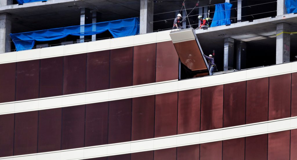 Construction workers install glass panels on the facade at the Wynn Resorts casino site in Everett, Mass., Thursday.