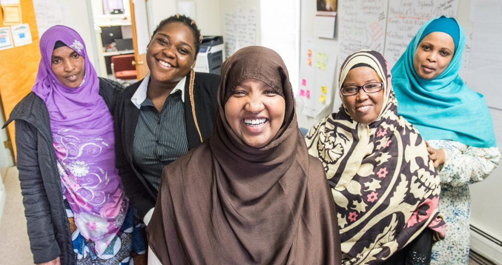 Fatuma Hussein, center, stands with co-workers at the Immigrant Resource Center of Maine on Lisbon Street in Lewiston. From left: Amina Farah, Bright Musuamba, Hussein, Zahra Houssein and Choukri Mohamed.