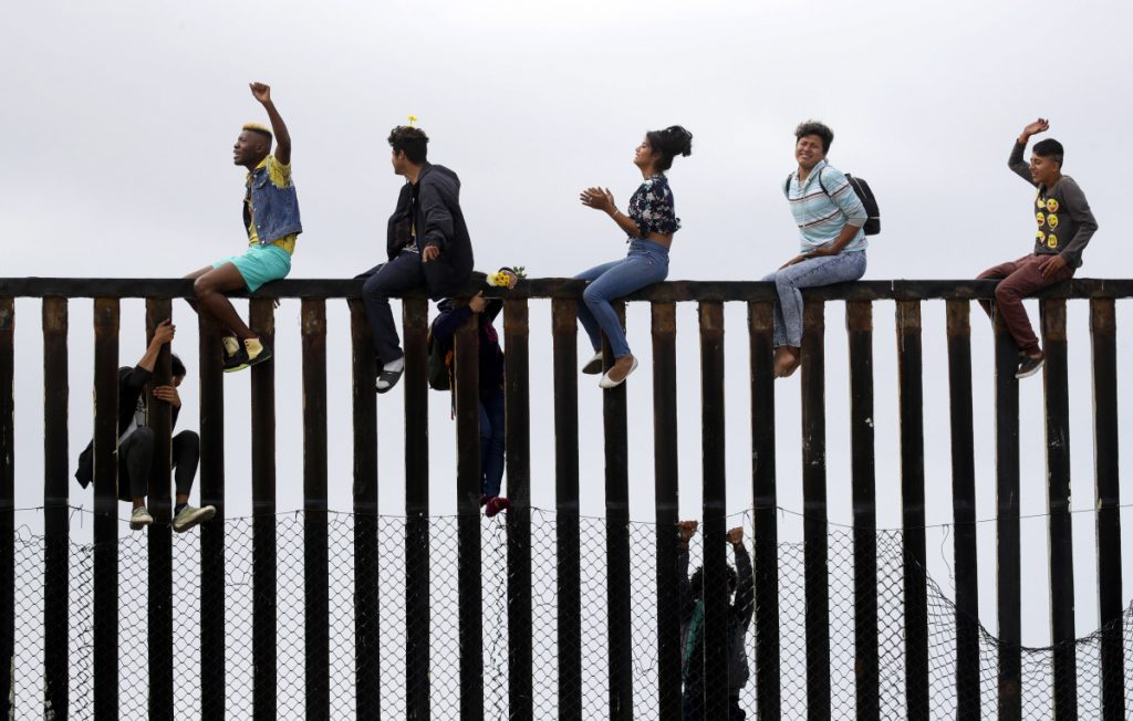 Central American migrants sit on top of the border wall on the beach in San Diego during a gathering of migrants living on both sides of the border Sunday.