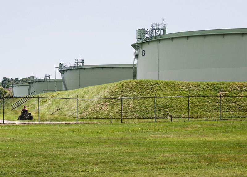 A mower cuts the grass at the Hill Street tank farm in 2015 in South Portland.