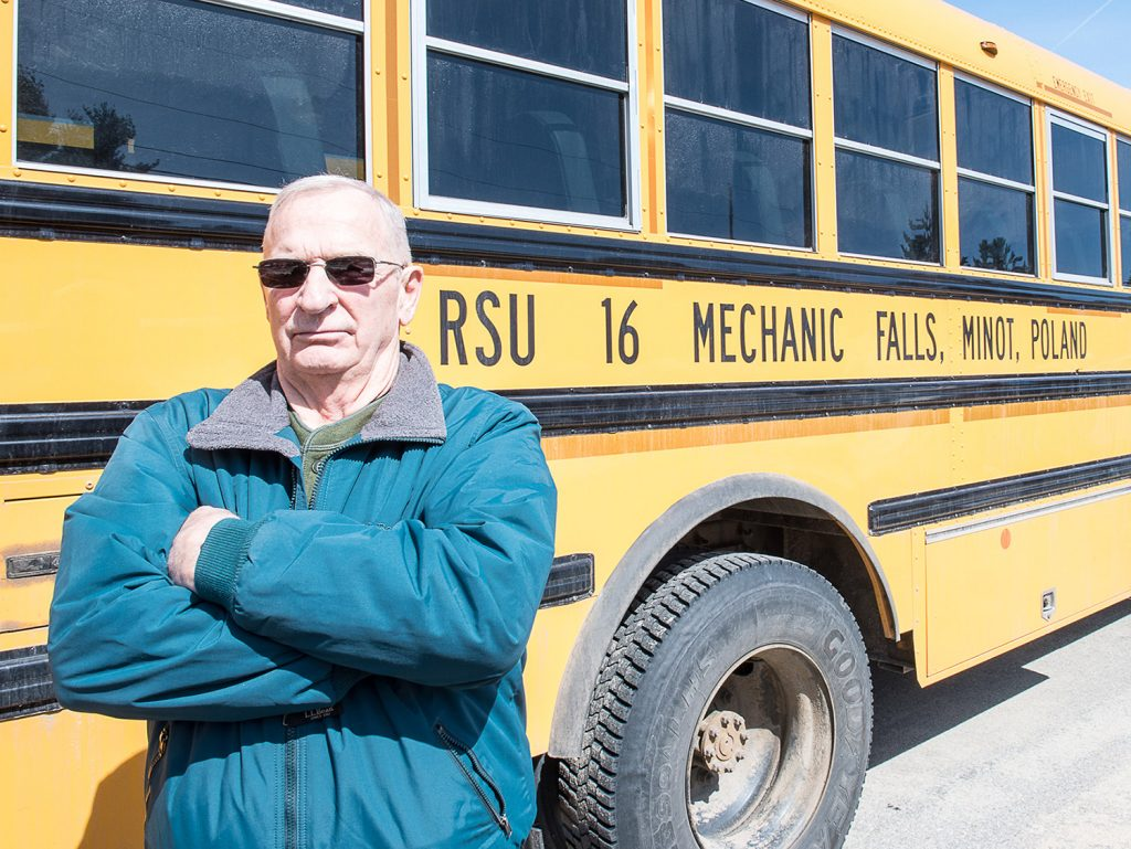 Mike Downing stands in the RSU 16 bus depot in Poland in March. Downing was fired in January for making racist and sexist comments and has since been elected to the board of the school system that fired him.