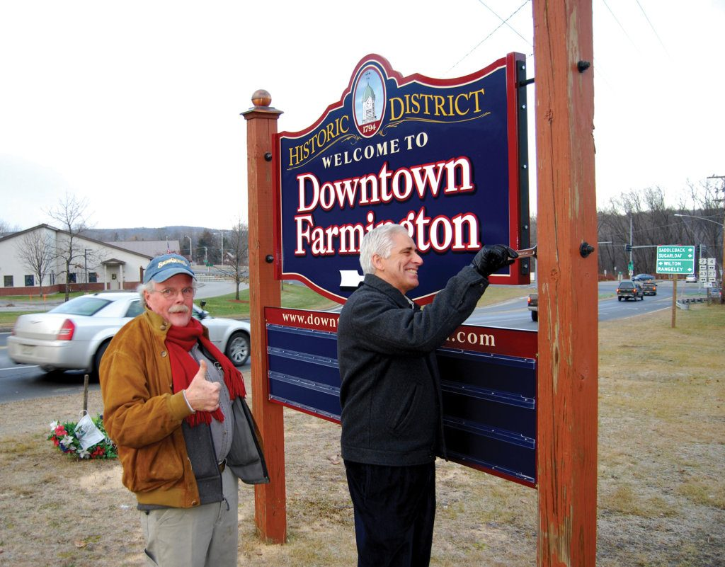 Mike Monahan gives a thumbs-up as Peter Judkins, president of Franklin Savings Bank, works on the Farmington Downtown Association sign. Monahan created many signs for the community and area businesses. He died March 26.