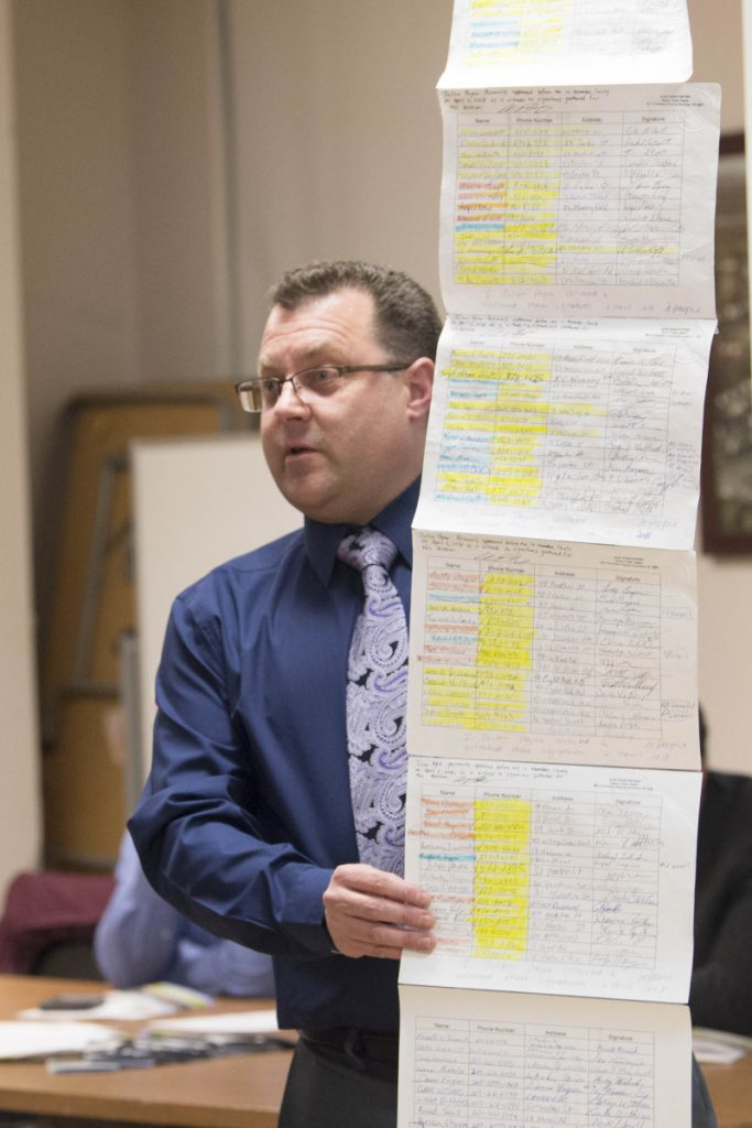 Julian Payne holds up a petition of supporters for his Ward 5 seat Tuesday as he speaks with residents in the City Council chamber during a council meeting in Waterville.