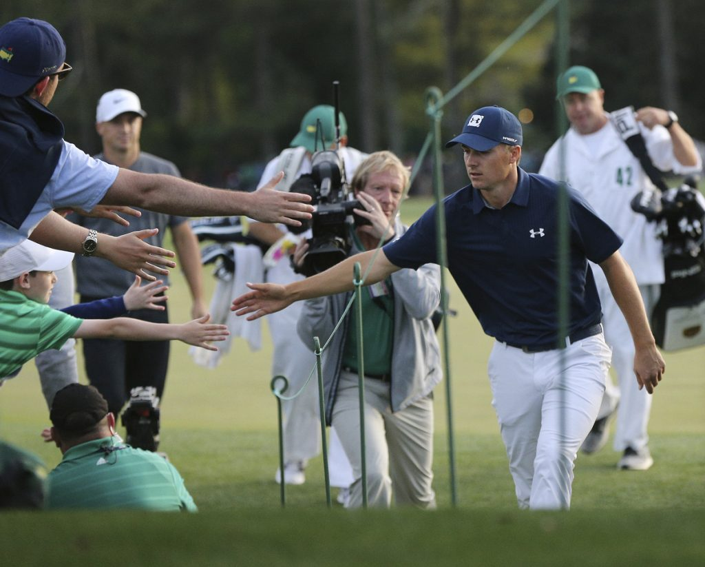 Jordan Spieth, front right, greets fans five as he leaves the 18th green during the first round at the Masters on Thursday in Augusta, Georgia.