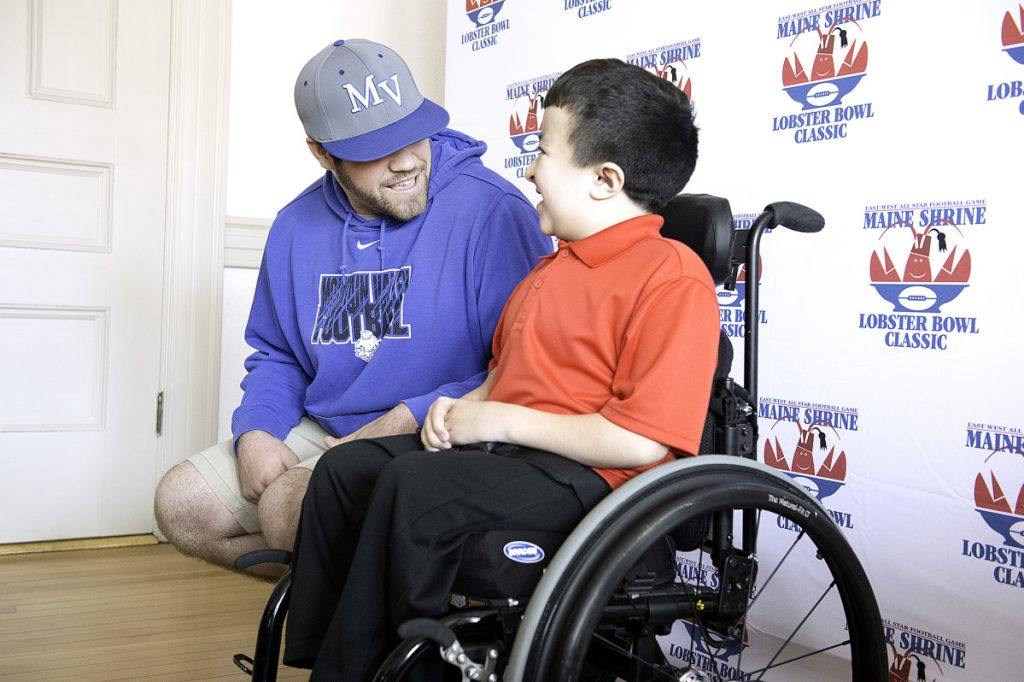 Sun Journal photo by Daryn Slover   Mountain Valley High School senior Curtis Gauvin, left, talks with special guest Alec Cabacungan during the annual Maine Shrine Lobster Bowl Classic team meeting Sunday in Lewiston.