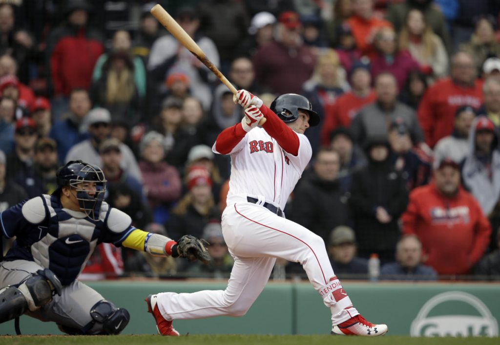 Boston's Andrew Benintendi, right, hits an RBI-double as Tampa Bay's Jesus Sucre, left, looks on in the eighth inning Sunday in Boston.