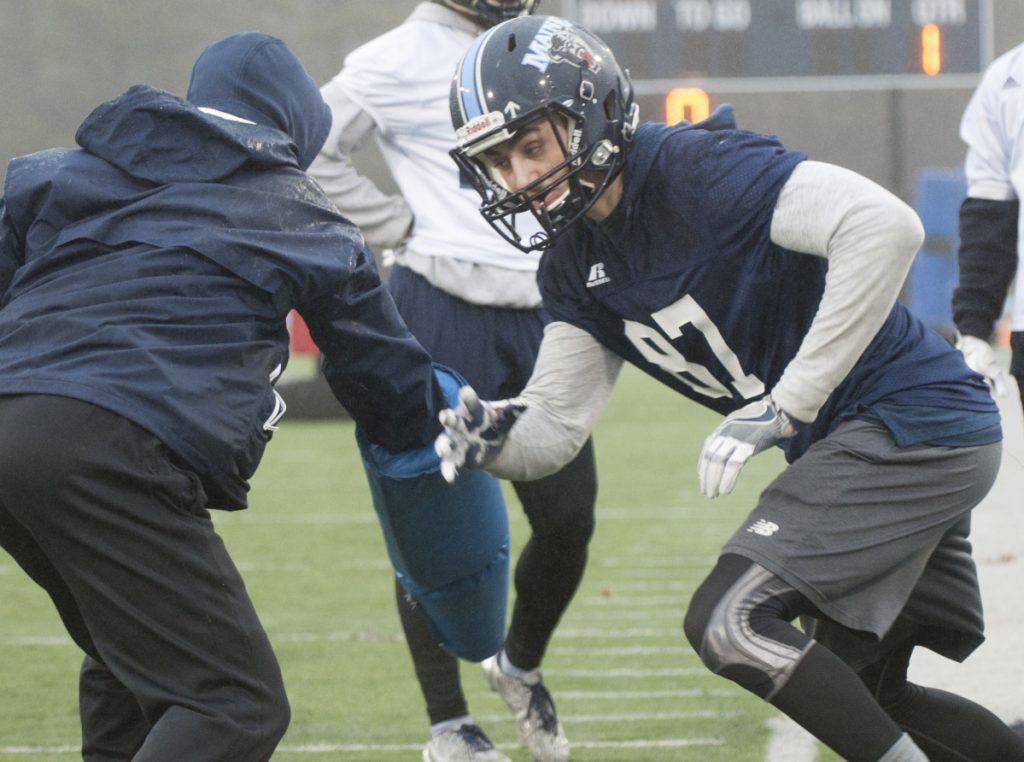 UMaine football player Hunter Smith joins his teammates on the rain soaked field for the first spring practice Wednesday in Orono.