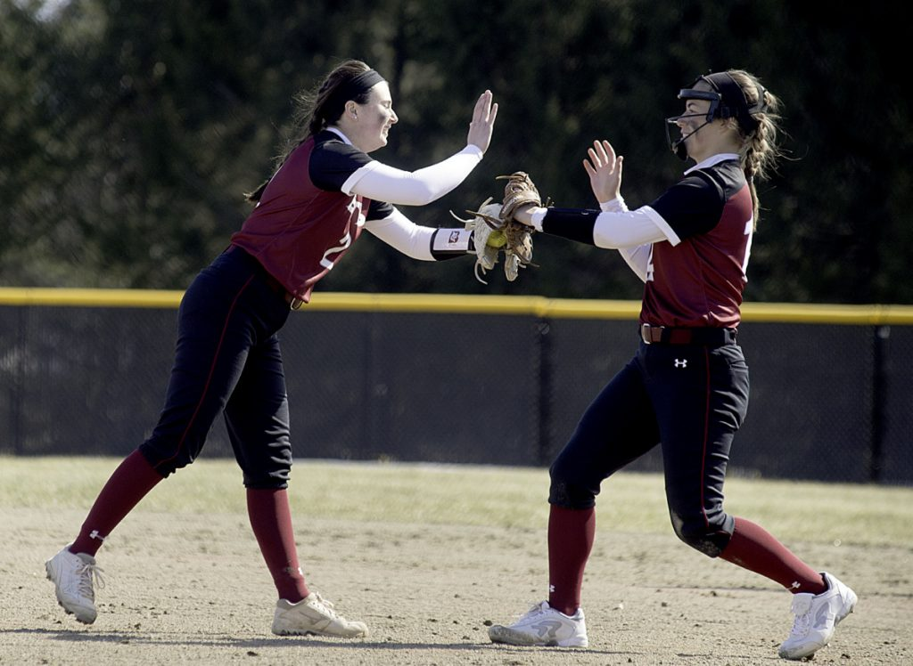 Sun Journal photo by Daryn Slover   Bates College pitcher Kirsten Pelletier, left, gives Payton Buxton a high five to close out the inning against Tufts on Saturday in Lewiston.