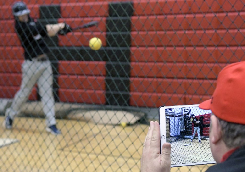 Hall-Dale High School coach Bob Sinclair records hitters during an April 4 practice.