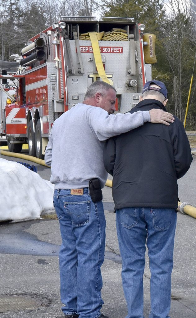 Dennis Wright, left, comforts his neighbor Ron Goguen on Thursday as firefighters from several departments battle a smoky fire that destroyed a mobile home rented by Goguen and his wife, Sandra, at China Lake Park in Vassalboro.