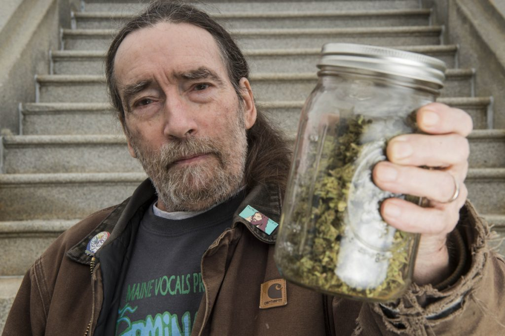 Donnie Christen poses for a portrait Friday in front of the Somerset County Courthouse in Skowhegan while holding an ounce of marijuana.