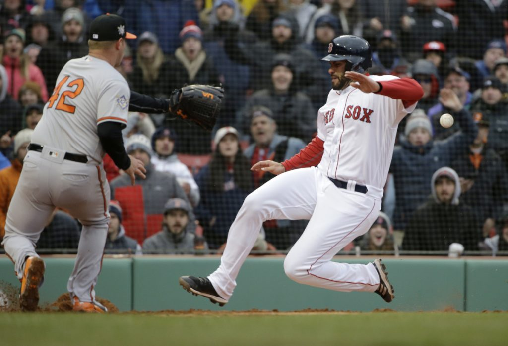 Boston's J.D. Martinez, right, scores on a wild pitch by Baltimore's Dylan Bundy, left, in the sixth inning Sunday in Boston.