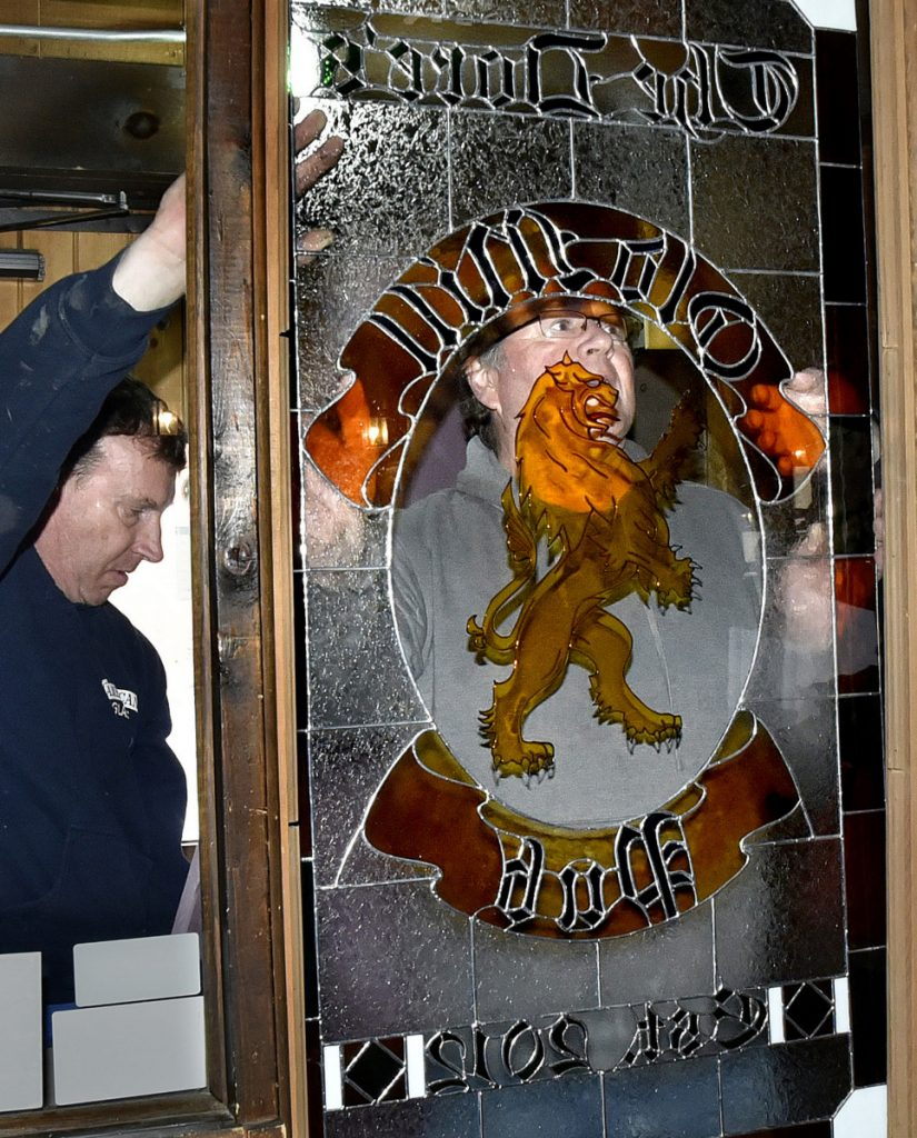 Old Mill Pub owner Greg Dore is seen in the center of a new stained glass window he and Bill Epp, left, installed at the Skowhegan restaurant on Monday. The original stained glass was removed and given to the McCarthy family who previously owned the business.