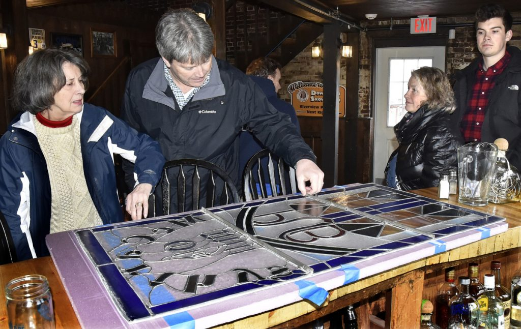 McCarthy family members, from left, Judie, Rick, Julie and Kael, look over the stained glass window that greeted customers inside the Old Mill Pub in Skowhegan that the family once owned after it was removed on Monday. Current owner Greg Dore gave the family the original window and replaced it with a new one.