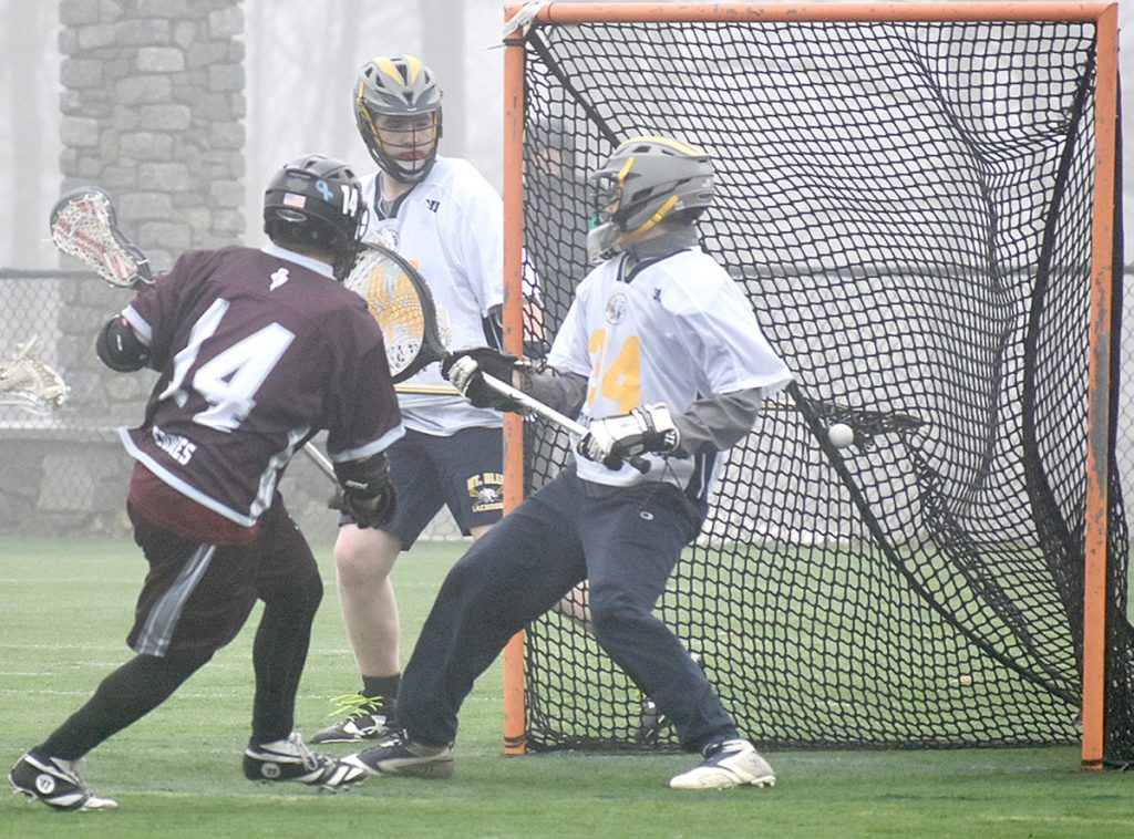 Edward Little's Ben Feldman (14) scores one of his three goals against Mt. Blue goalie Brian Hayes (34) on Tuesday at Kents Hill School.