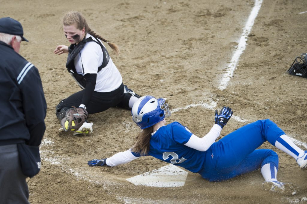 Lawrence's Megan Curtis (2) slides safely across home plate before Maine Central Institute catcher Maria Reed can apply the tag Friday in Fairfield.
