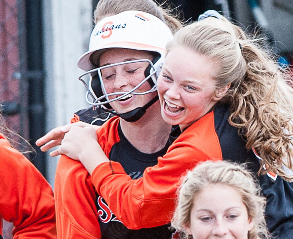 Skowhegan pitcher Ashely Alward, left, is mobbed by teammates after hitting a home run against Lewiston on Friday at Bates College. Alward also pitched a no-hitter for the Indians.