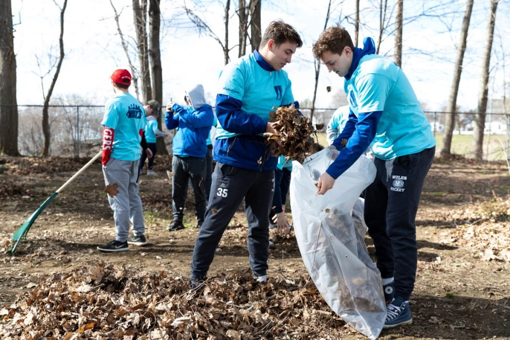 Joe MacDonald, left, of Westford, Mass., fights to put leaves into a bag held by Jake Rasch, of Cumberland. Both are freshmen hockey players at Colby College and were participating Saturday in Colby Cares Day at the Waterville Historical Society's Redington Museum.