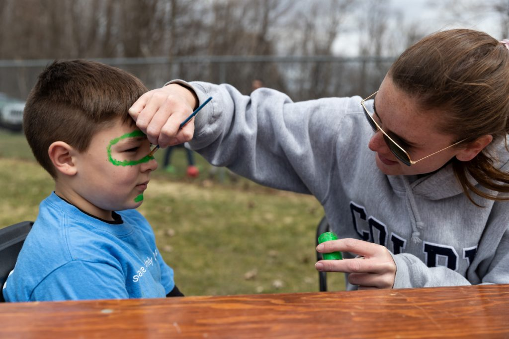 Sarah Taft, co-director of the Volunteer Center at Colby College, paints a snake Saturday onto the face of Gideon McGee, of Waterville, during Colby Cares Day at Couture Field on Water Street, where a public lunch was served after students finished their morning service projects.