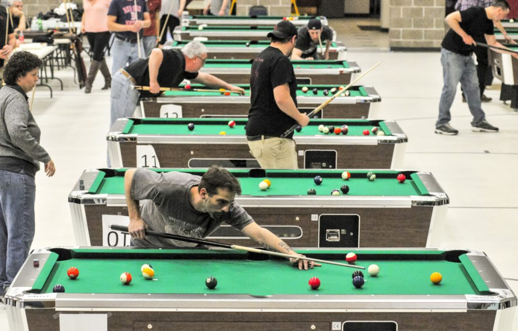 The top four finalist teams in three divisions compete on many tables during a pool tournament on Sunday in the Augusta Armory.